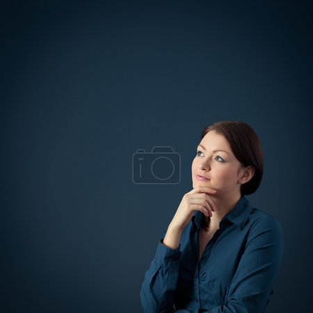 Photo for Young woman think (contemplate) about something, blue background. - Royalty Free Image