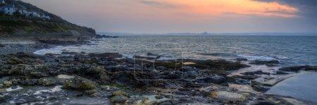 Panorama landscape of rocky coastline at sunrise