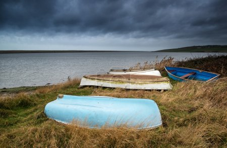Old decayed rowing boats on shore of lake with stormy sky overhe