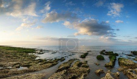 Photo pour Paysage panoramique donnant sur la mer avec un littoral rocheux et un ciel magnifique au coucher du soleil - image libre de droit