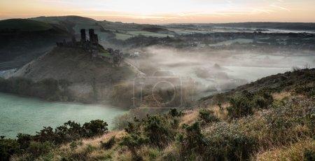 Medieval castle ruins with foggy landscape at sunrise