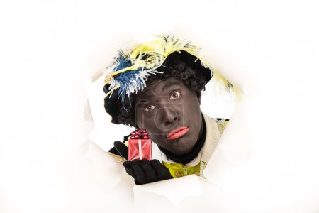 Photo for Zwarte piet ( black pete) Looking through hole .typical Dutch character part of a traditional event celebrating the birthday of Sinterklaas in december - Royalty Free Image