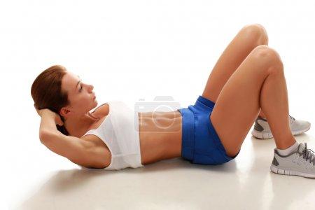 Photo pour Jeune modèle attrayant de remise en forme effectuant des exercices abdominaux couchés sur le sol - image libre de droit