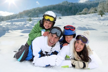 Photo for Happy family laying down in the snow - Royalty Free Image