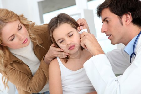 Photo for Doctor looking at little girl ear infection - Royalty Free Image