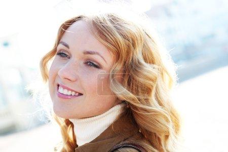 schöne blonde Frau in der Stadt bei sonnigem Tag