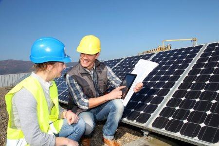 Foto de Hombre mostrando tecnología de paneles solares a chica estudiante - Imagen libre de derechos