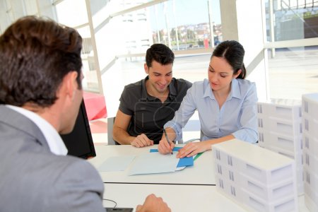 Photo for Couple in real-estate agency signing property loan contract - Royalty Free Image