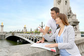 Couple reading tourist map on the Bridge Alexander the Third
