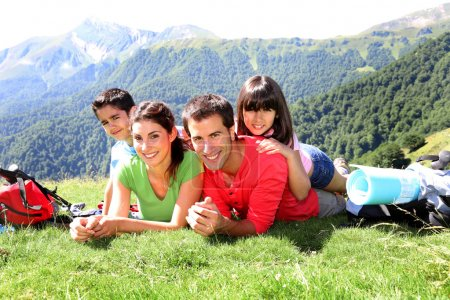 Portrait of happy family laying on the grass in mountain