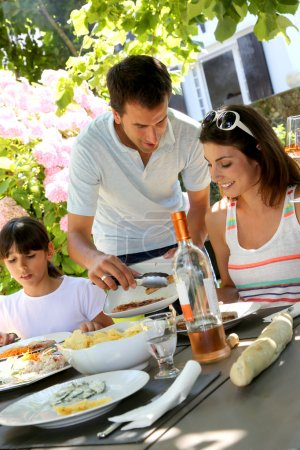 Father serving grilled meat to family
