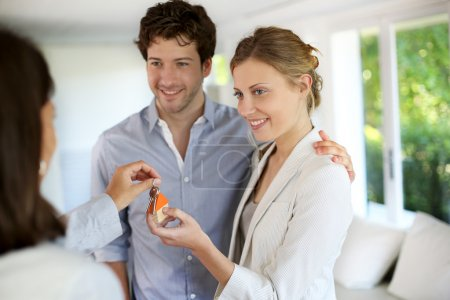 Happy young couple getting keys of their new home
