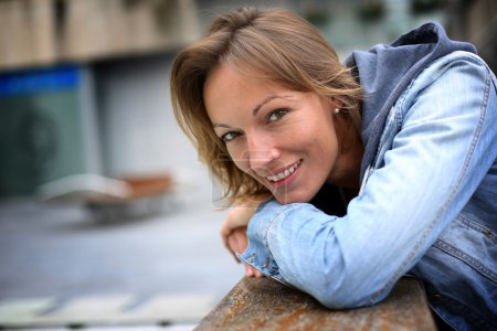 Photo for Smiling adult woman with blue jeans jacket in town - Royalty Free Image