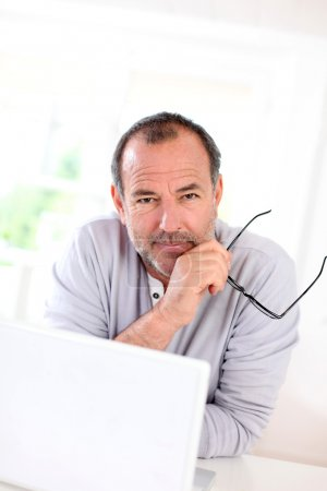 Photo for Senior businessman working on laptop from home - Royalty Free Image