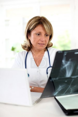 Woman doctor in office checking XRay