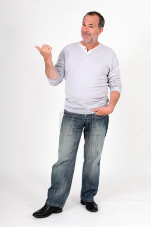 Senior man standing on white background and pointing at message