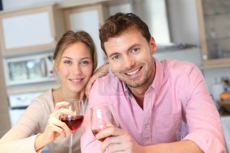 Happy couple cheering with glass of wine