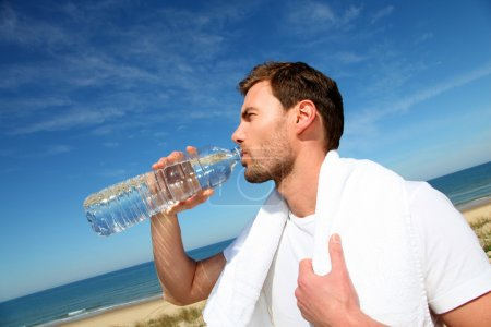 Portrait of jogger drinking water from bottle