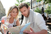 Couple sitting at a coffee shop terrace to look at map