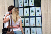 Couple looking at house-for-sale ads through shop window