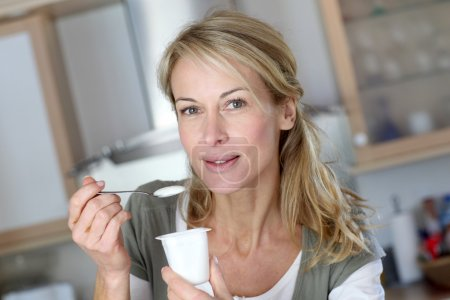 Portrait of middle-aged woman eating yoghurt