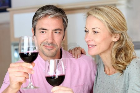 Couple drinking red wine in kitchen