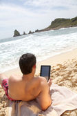Man using electronic tablet on the beach