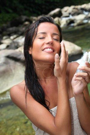 Closeup of beautiful woman applying cosmetic cream on her face