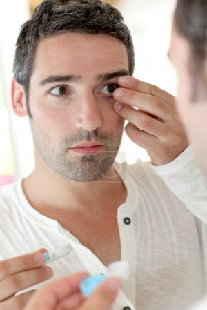 Man in front of mirrror putting ocular lens