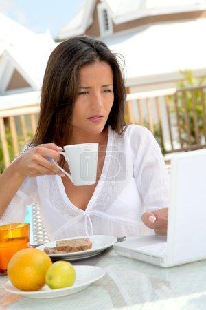 Photo pour Belle femme connectée sur internet tout en prenant le petit déjeuner - image libre de droit