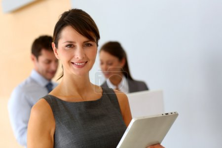 Businesswoman standing in corridor with tablet