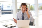 Happy businessman on the phone in front of laptop