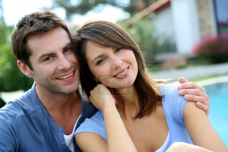 Photo for Cheerful couple sitting in front of new house - Royalty Free Image