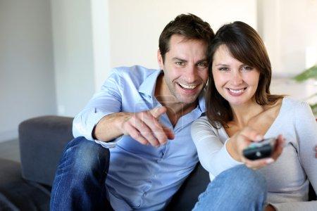 Photo pour Couple assis dans le canapé en choisissant le programme tv - image libre de droit