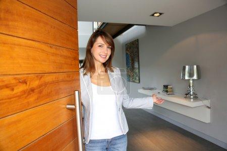 Photo pour Femme ouvert sa porte de maison d'accueillir - image libre de droit