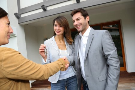 Photo pour Nouveaux propriétaires serrant la main à l'agent de vente - image libre de droit