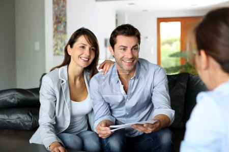 Couple meeting architect for plans of future home
