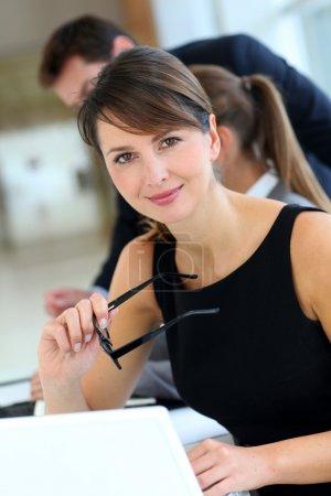 Attractive businesswoman sitting in office with workteam