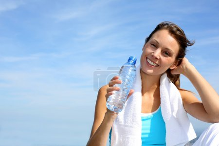 Photo for Thirsty fitness girl holding bottle of water - Royalty Free Image