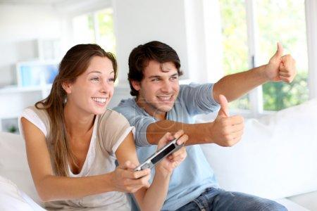 Photo pour Jeune couple de jeux vidéo à la maison - image libre de droit
