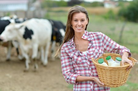 Photo for Smiling young farmer carrying bottles of fresh milk - Royalty Free Image