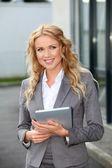 Podnikatelka stojí venku s elektronickým tablet