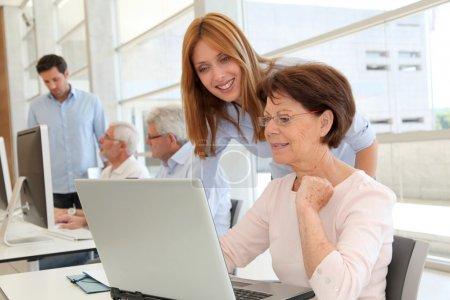 Photo pour Femme senior avec formateur en face de l'ordinateur portable - image libre de droit