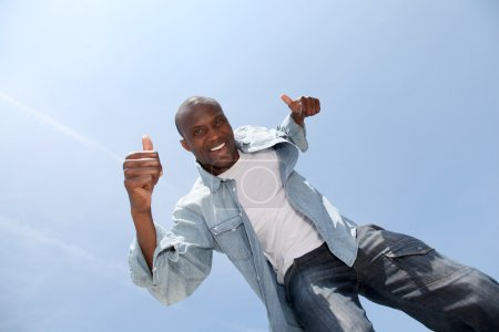 Foto de Hombre mostrando pulgares hacia arriba con cielo azul - Imagen libre de derechos