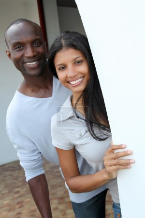 Cheerful couple standing by house entrance door