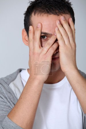 Closeup of young man hiding face whit hands