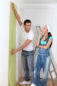 Jeune couple en choisissant la couleur du papier peint