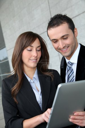 Business meeting outside with electronic tablet