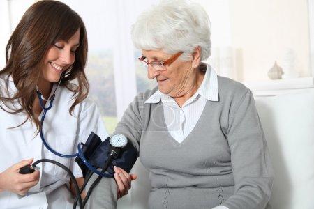 Photo pour Gros plan de l'infirmière vérifiant la pression artérielle de la femme âgée - image libre de droit
