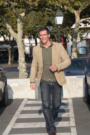 Man crossing the street in town on crosswalk